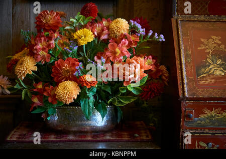 A rustic country flower arrangement beside a red and orange antique chinese cabinet - Stock Photo