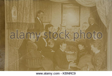 American archive monochrome photo of a group of people in a parlour enjoying entertainment.  A woman is playing - Stock Photo