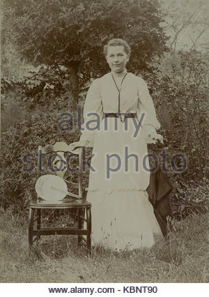 American archive monochrome photo of a young woman or girl standing next to a chair in a garden A fan is on the - Stock Photo