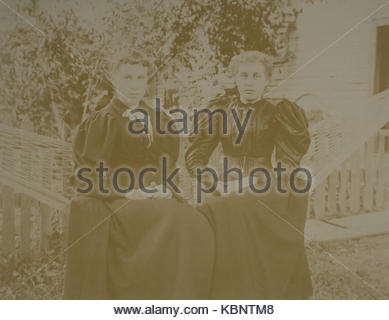 American archive monochrome photo of two young women sitting in a garden  hammock with hands clasped in their laps, - Stock Photo