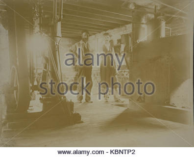 American archive monochrome photo of two men named as engineers in an industrial room next to machinery. Taken in - Stock Photo