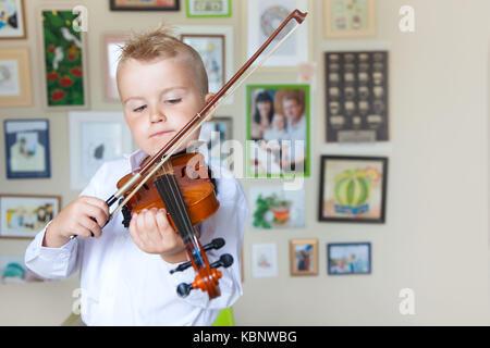 child playing violin, black background, sentimental theme, sad