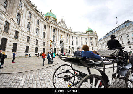 Famous horse-drawn carriage called fiaker passes by the Hofburg palace at Michaelerplatz in Vienna with tourists - Stock Photo