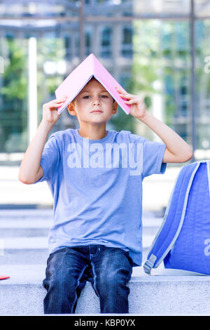 Little schoolboy with book on his hand sitting outdoors - Stock Photo