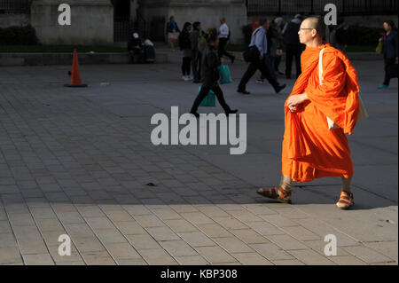 Two Buddhist monks are sightseeing in Trafalgar Square, they are taking pictures of each other. - Stock Photo