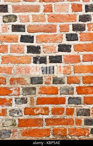 Old grunge red brick wall with black crossing diagonal lines - Stock Photo