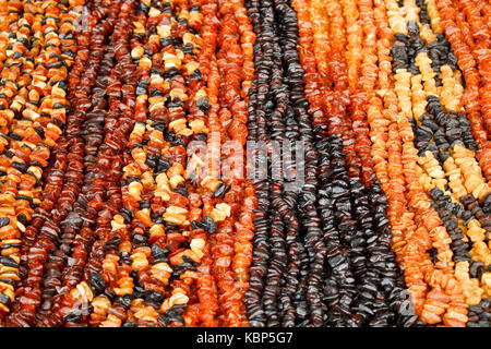 Amber beads of various colors for sale on lithuanian market. - Stock Photo