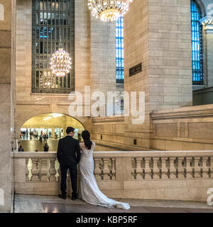 New York, USA,  29 September, 2017.  Newlyweds watch passers-by in New York's Grand Central Station. Photo by Enrique Shore