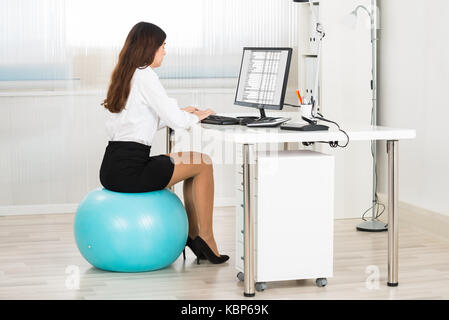 Side view of young businesswoman using computer while sitting on pilates ball in office - Stock Photo