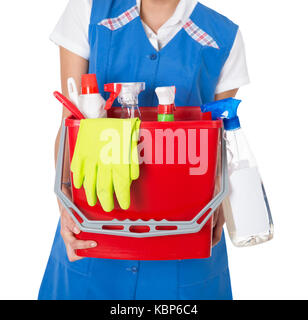Midsection of female janitor carrying bucket with cleaning equipment against white background - Stock Photo