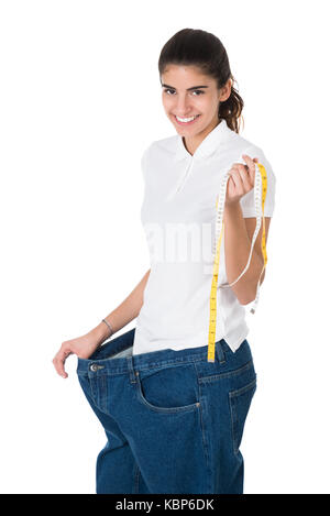 Portrait of smiling young woman with tape measure showing her old jeans on white background - Stock Photo