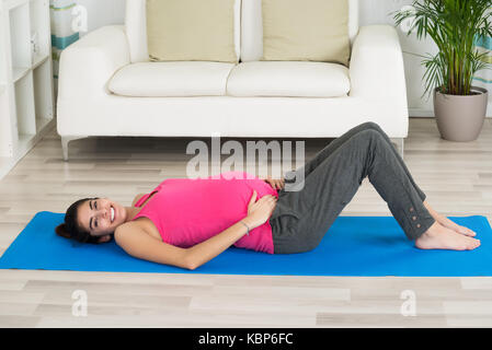 Side view portrait of happy pregnant woman lying on exercise mat at home - Stock Photo