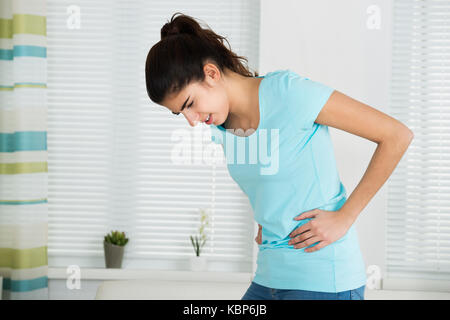 Young woman suffering from stomach ache standing at home - Stock Photo
