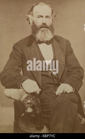 American archive monochrome studio portrait of old man with a beard sitting in a chair, named as Grandpa Bennett, - Stock Photo