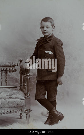 American archive monochrome studio portrait photograph of young boy wearing a jacket, britches and bow tie standing - Stock Photo