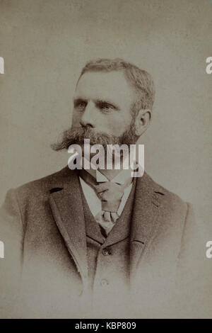 American archive monochrome studio portrait photograph of a man with handlebar moustache and beard wearing a suit - Stock Photo