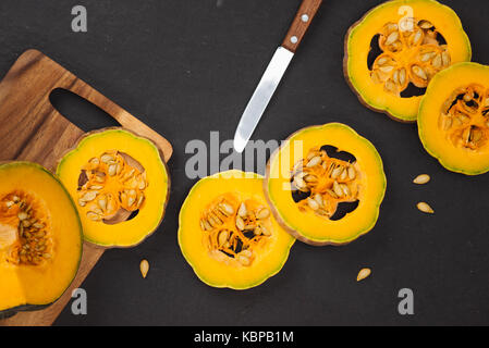 Delicious fresh pieces of ripe pumpkin on wooden background - Stock Photo