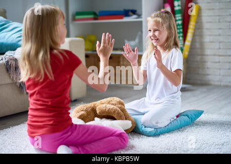 Portrait of two cute little sisters playing pat-a cake sitting on floor on thick plush carpet in cozy living room - Stock Photo
