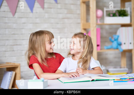 Portrait of adorable little sisters looking at each other tenderly while reading book together in cozy playroom - Stock Photo