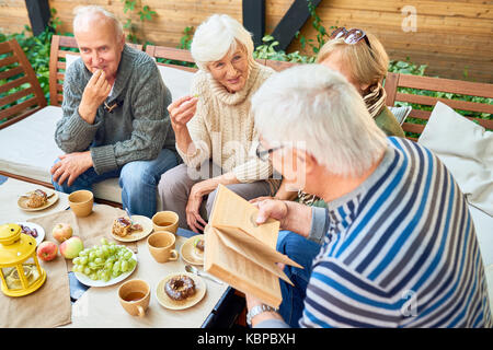 Group of joyful senior friends having fun outdoors: they enjoying delicious pastry and fragrant coffee while elderly - Stock Photo