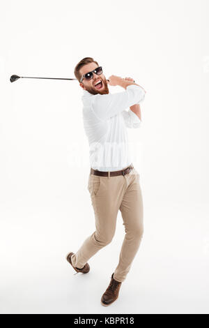 Picture of handsome young screaming emotional bearded man standing over white wall background isolated holding golfstick. - Stock Photo