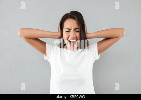 Angry irritated asian woman covers her ears with hands and shouting while standing isolated over gray background - Stock Photo