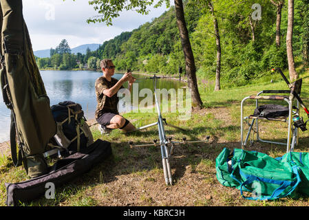 Fishing adventures, carp fishing. Angler with camouflage t-shirt, is fishing with carpfishing technique in freshwater. - Stock Photo