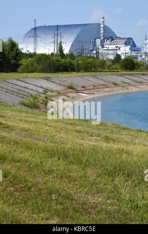 The sarcofagus of reactor 4 in the Chernobyl power Pland, with Prypiat river in the foreground, Ukraine. - Stock Photo