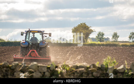 Farm worker driving tractor ploughing field in East Lothian, Scotland, United Kingdom - Stock Photo