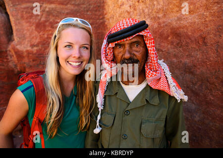 Tourist girl poses with old man, Bedouin, at colourful rock-formations in Petra, Wadi Musa, Jordan - Stock Photo