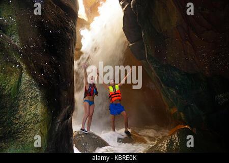 Young couple under waterfall at the canyon of Wadi Mujib, Jordan - Stock Photo