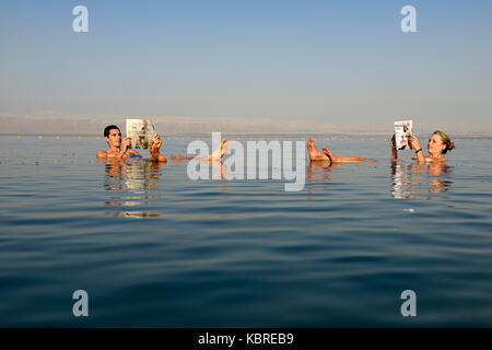Young couple reads newspaper floating in Dead Sea, Jordan - Stock Photo