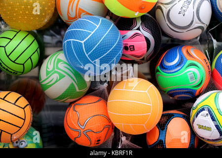 Lots of colourful kids footballs for sale outside a toy or sports store - Stock Photo