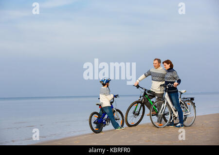 Young family of three riding bicycles on beach - Stock Photo
