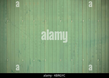 green corrugated metal wall or fence. background and texture. vintage tone. - Stock Photo