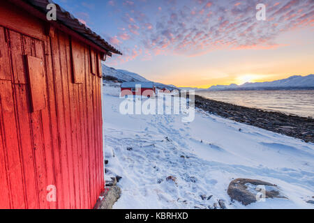 Sunset among the fishermen's houses overlooking the fjord. Nordmannvik, Kafjord, Lyngen Alps, Troms, Norway, Lapland, - Stock Photo