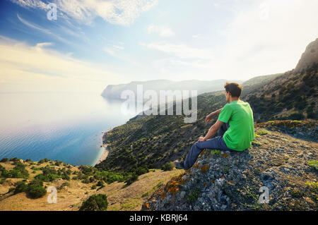 Traveler relax on the mountain edge. Nature and adventure composition - Stock Photo