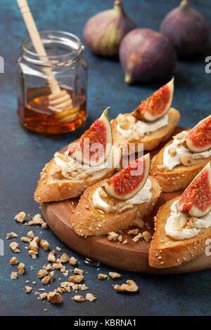 sandwiches with figs, ricotta, honey, walnut, fresh figs and a jar of honey on a blue background - Stock Photo