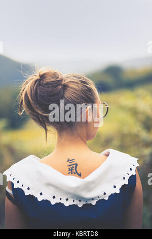 Blonde girl in a blue blouse in the countryside. - Stock Photo