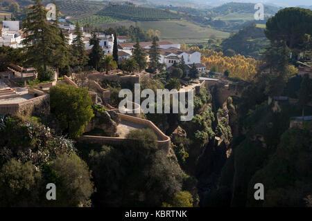 Ronda, Spain: View of the Jardines de Cuenca perched over El Tajo Canyon from the Puente Nuevo in La Ciudad. - Stock Photo