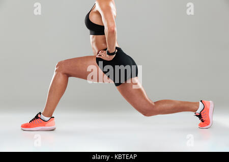 Cropped side view image of a young fitness woman doing lunge exercises isolated over gray background - Stock Photo