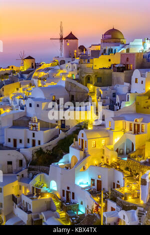 Aerial view of  Oia town, Santorini island, Greece at sunset. Traditional and famous white houses and churches  - Stock Photo