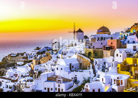 Sunset in Oia town, Santorini island, Greece. Traditional and famous white houses and churches  with blue domes - Stock Photo