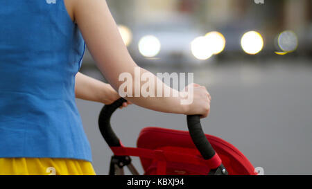 Young mother walking with baby carriage at the street back view close up. Mother with a stroller walks down the - Stock Photo