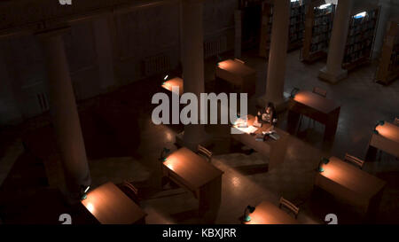 Top view of student hand writing a book with laptop at library. Girl sitting in empty library at night top view - Stock Photo