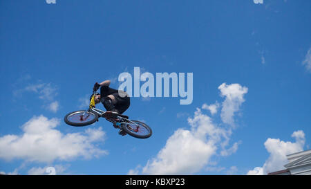 Young man on BMX bike jumps. Man doing twists and tricks on bmx in slow motion blue sky background - Stock Photo