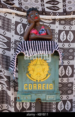 Traditional Brazilian green metal mailbox, post office postal box, with a flirting namoradeira in Congonhas do Campo, - Stock Photo