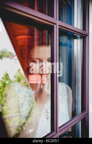Young attractive dark hair lady looking through a window. Vertical close-up portrait. Young woman looking down a - Stock Photo