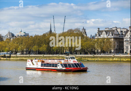Red and white City Cruises tourist sightseeing boat cruises along the River Thames by Victoria Embankment, London - Stock Photo
