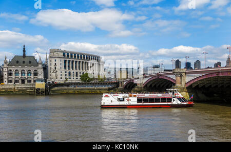 Red and white City Cruises tourist sightseeing boat on the River Thames sails under Blackfriars Bridge by Unilever - Stock Photo